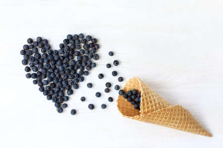 blueberries are strewed at desk of the waffle cone top view  heart of berries to the holiday Stock Photo