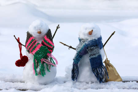 drifts: two  smile snowmen in scarves against the background of the snow drifts  fun walk together