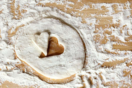 farinaceous: blank heart shape of farinaceous dough on a wooden table  cooking pastry for the holiday