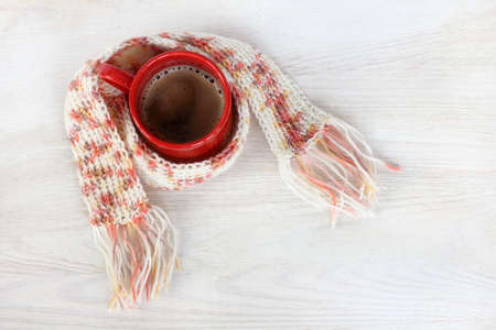 coffee in a red mug, wrapped in a warm scarf knitted top view  soft warming drink Stock Photo