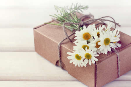 Holiday gift with a bouquet of field daisies on a desk  congratulations in retro style