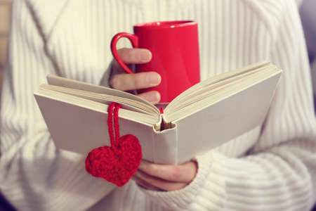 man wearing a white sweater love reading a book and drinking a hot drink  favorite pastime at home