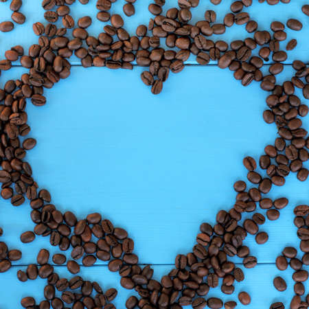 coveted: flat layout of the roasted beans forming a heart shape on blue wooden surface  favorite brand coffee Stock Photo