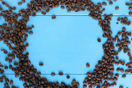 coveted: empty frame of roasted beans on the background of blue wooden plank top view  coffee background gourmet