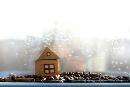 toy house on the hill of beans in the background window with raindrops  cozy place for coffee break
