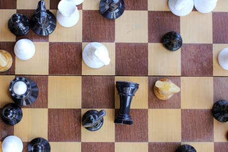 Black chess piece on the board fell, surrounded by three different horses, top view / unexpected denouement Party 스톡 콘텐츠