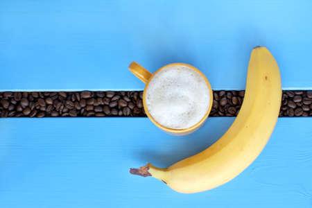 揚げ豆とバナナの青いテーブルの上の泡のカプチーノの黄色のマグカップとフラットなレイアウト補強食欲をそそるコーヒーブレイク