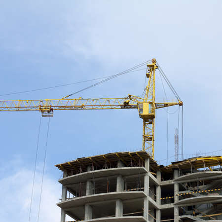 under construction high-rise building with a yellow crane on the background of the sky  next height level