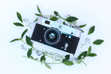 black and white photograph: Old shabby film camera decorated with flowers and leafs top view  spring season for photographers Stock Photo