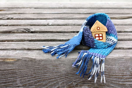 Small house in a warm scarf on a very old wooden surface  warming atmosphere for living Stock Photo