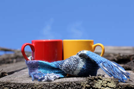 Red and yellow mug wrapped in a scarf against the sky  hot drinks in the fresh air