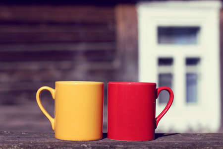 Two mugs stand on a table on the background of an old wooden house in the street in the afternoon  coffee pause in the fresh air