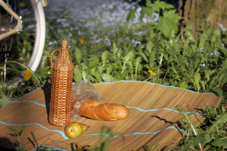 matting: Wicker mat with a retro bottle, white bread, and a pear on the background of a forest landscape  picnic outside the city