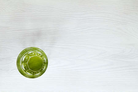 Clean water in a green glass on a white wooden table top view  ecological drink Stock Photo