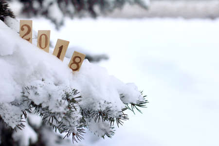 snow-covered Christmas tree decorated with wooden numeric  that indicate the coming of the new year  winter atmosphere 2018