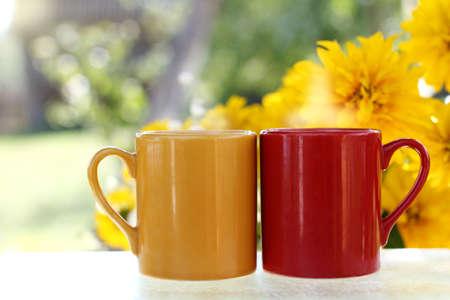 花の背景の通りテーブルの上に立つ夏休みホットド リンクは 2 つのマグカップ