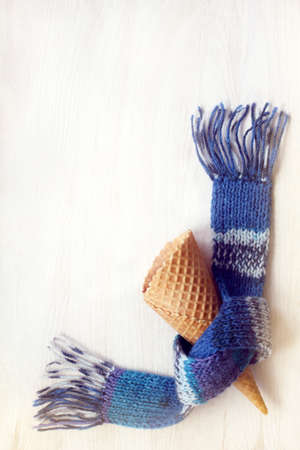 Empty wafer cone wrapped in blue scarf  for winter ice cream