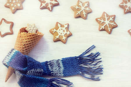Waffle horn in a blue scarf and many festive cookies  sweet Christmas dessert