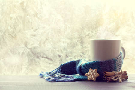 Cinnamon, gingerbread and white mug wrapped in a scarf, stands on a table on the background of a frozen window  Warming atmosphere of winter holidays