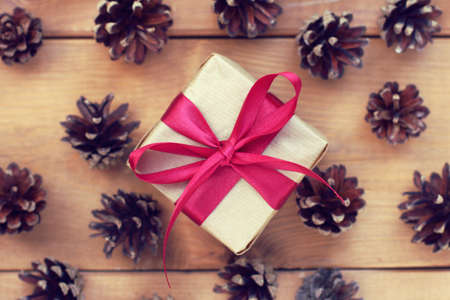 gift wrapped in craft paper tied with a red bow against the background of fir cones  Christmas surprise