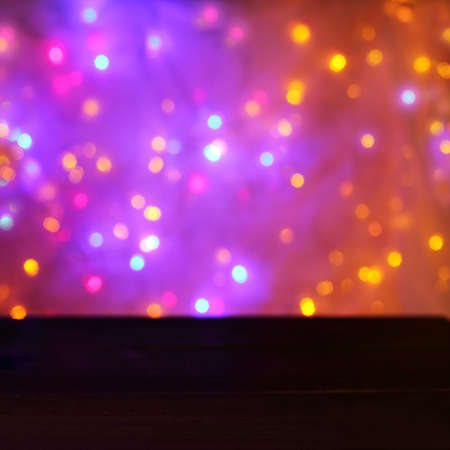 set of multicolored blurred light sources against the background of an empty table  Christmas festive lights