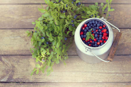 full can of blueberries and strawberries on the table top view  harvest of wild berries