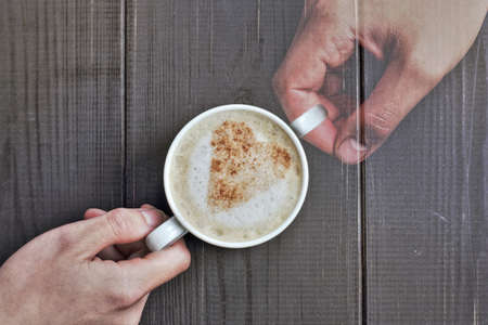 real and imaginary hand with a cup of frothy cappuccino and a heart symbol from cinnamon  memories of your favorite moments