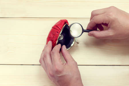 viewing through a magnifying glass, a slightly opened red purse with one coin  small last savings