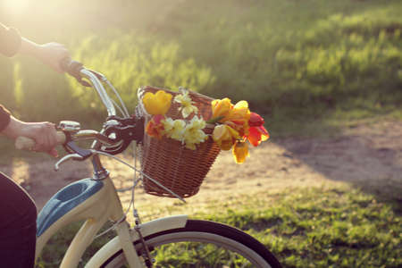 blur in motion cyclist is busy transporting flowers in a wicker basket at sunset in the park  ecological delivery of bouquets
