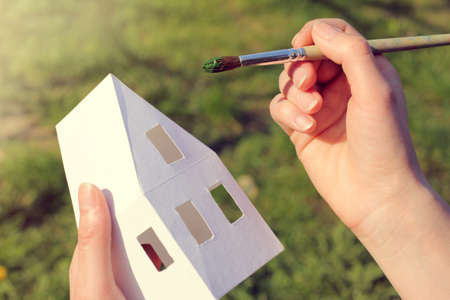 artist paints the layout of the house with a fine tassel  green color solution Stock Photo