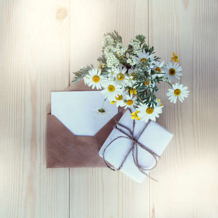 gift with a bouquet of chamomiles and an open letter for wishes on the table top view set for holiday