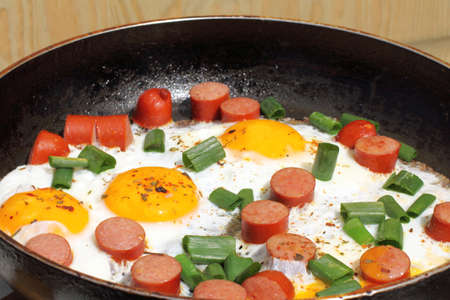 fried eggs with sausages and onion in a frying pan  hot rustic dish Stock Photo