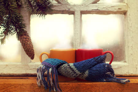 two mugs in scarf on the background of a fir branch and an old window morning   warming atmosphere of a winter vacation
