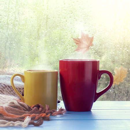 赤と黄色のマグカップをテーブルの上雨の後濡れている窓に敷物に次地球温暖化は、秋のドリンクします。 写真素材