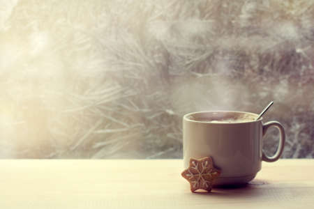 foamy steaming coffee with milk in a white mug is on the table opposite the frozen window  warming drink for winter morning