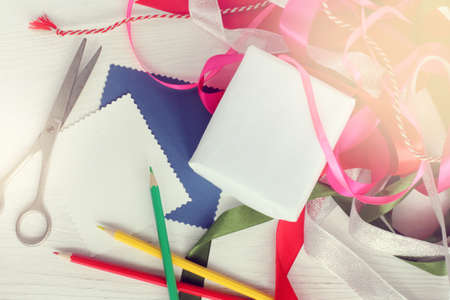 blank for gift with card, pencils, scissors and colored ribbons on table top view preparation for the holiday Stock Photo