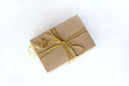 kraft box with bandaged gilded bow on a light table top view  Universal holiday surprise