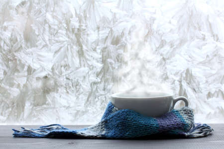 white mug in a blue scarf and warm steam in the form of a Christmas tree against the background of a frozen window warming Christmas fantasy