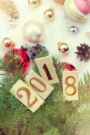 green spruce branches with wooden numbers on the background of festive decorations  with the new 2018 year