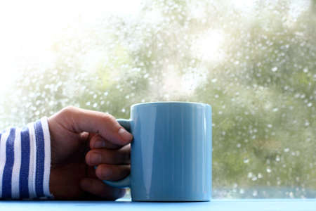 hand in striped sweater with and blue cup on table, against the window with drops after rain  autumn mood in a marine style