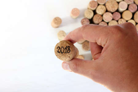 hand holds a large cork, from the sparkling wine, with the number  new year 2018