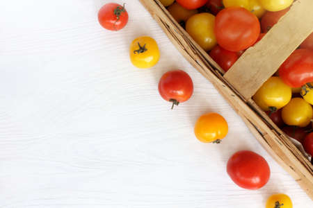 red and yellow tomatoes in a basket and on a table top view autumn harvest of ripe vegetables