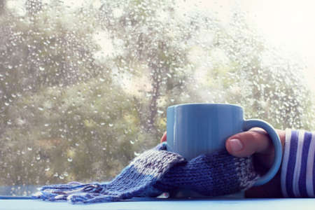 hand in striped sweater with cup wrapped in scarf against the window with drops after rain  warming atmosphere in blue tones