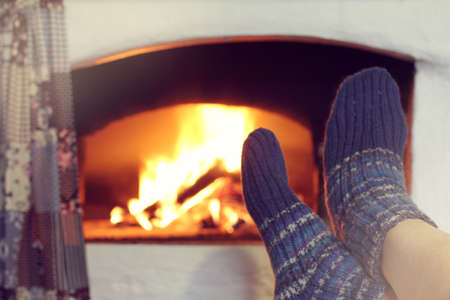 Human  warms his feet in blue socks on background  burning oven  cozy atmosphere of winter holidays