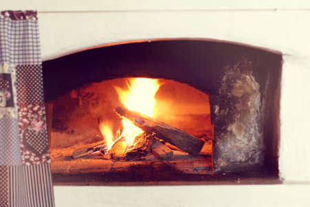 burning firewood in a large Russian stove  warming atmosphere in retro style