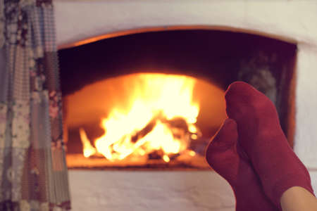 man warms his feet in red socks next to a burning fireplace  warming atmosphere of home comfort