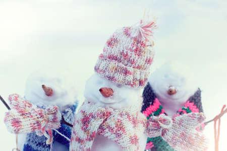 funny snowmen in warm scarves in winter holiday festivities on vacation