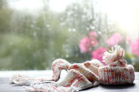 warm scarf and hat lay on a table against the window with drops after rain after autumn comes winter