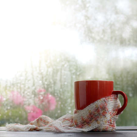 red mug wrapped in a pink scarf on the background of a window wet after a rain  Autumn warming drinks