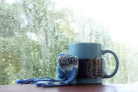 blue mug in a scarf on the background of a window with drops after an autumn rain  warming hot drink